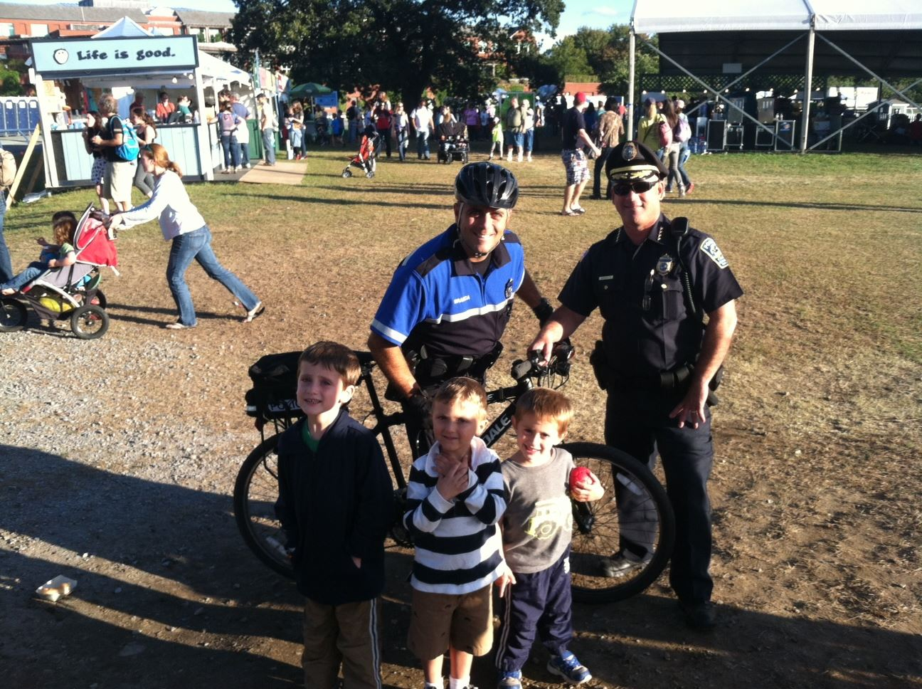 Two Police Officers Posing for a Photo With a Bike and a Few Kids